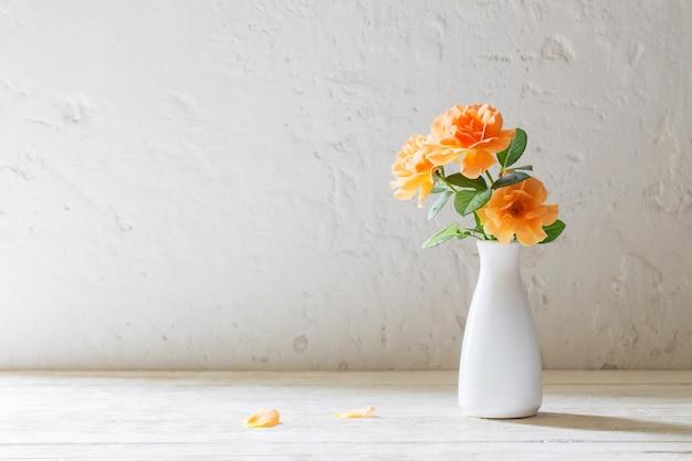 Rozen in vaas op witte muur