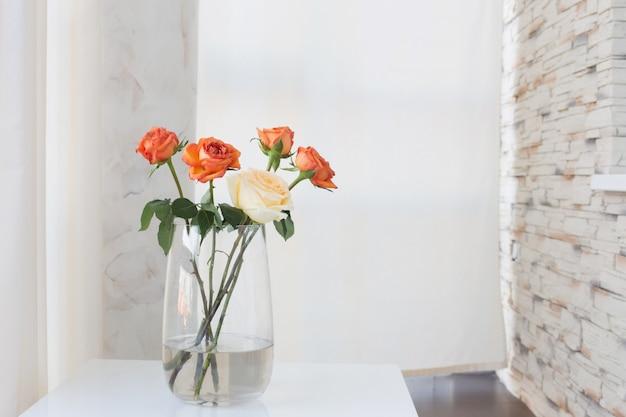 Rozen in vaas op witte tafel