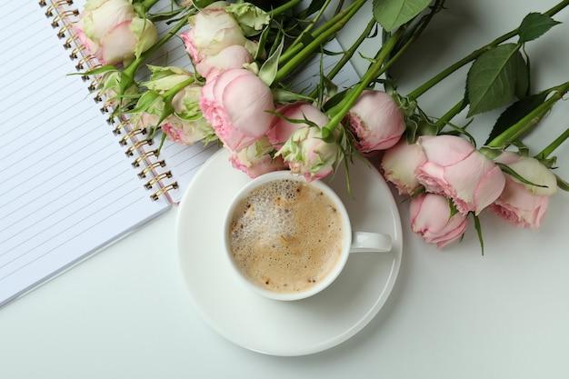 Rozen, kopje koffie en voorbeeldenboek op wit