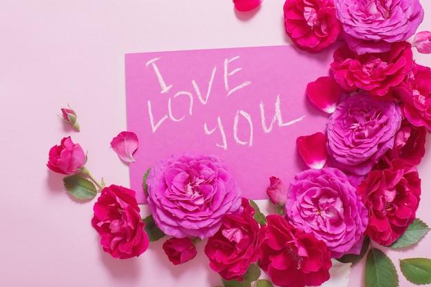 Rozen op roze achtergrond met liefdesverklaring
