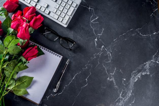 Rozen, rekenmachine, laptop en glazen op marmer