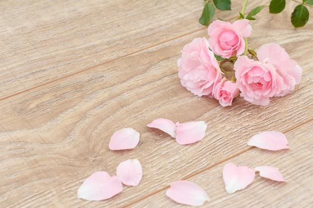 Rozenblaadjes en mooie rozen op de houten achtergrond. concept van het geven van een geschenk op vakantie. bovenaanzicht.