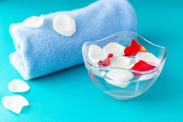 Rozenblaadjes in een kom met water en een handdoek.