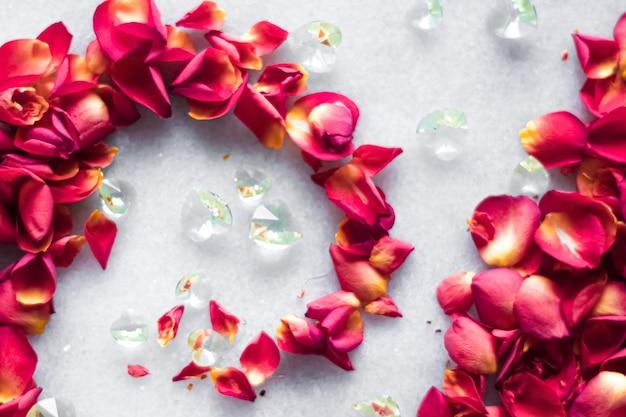 Rozenblaadjes op marmeren achtergrond bloemendecor en bruiloft flatlay vakantie wenskaart achtergrond voor...