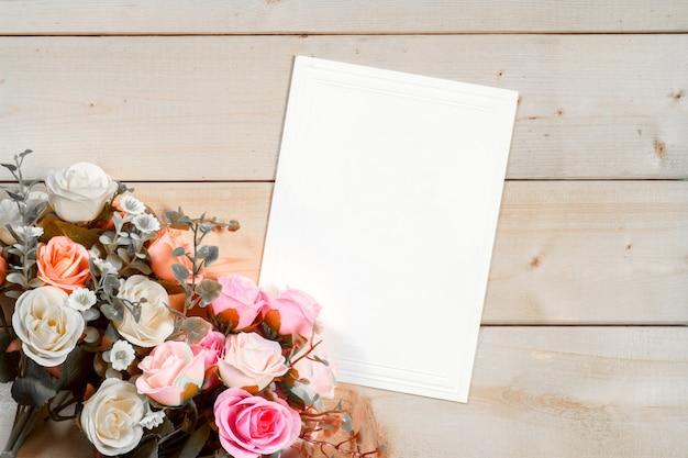 Rozenbloemen en lege markering voor uw tekst op houten achtergrond