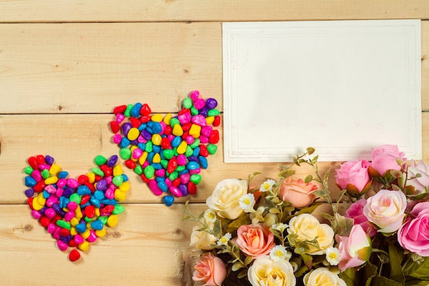 Rozenbloemen en lege markering voor uw tekst op houten achtergrondpastelkleurtoon