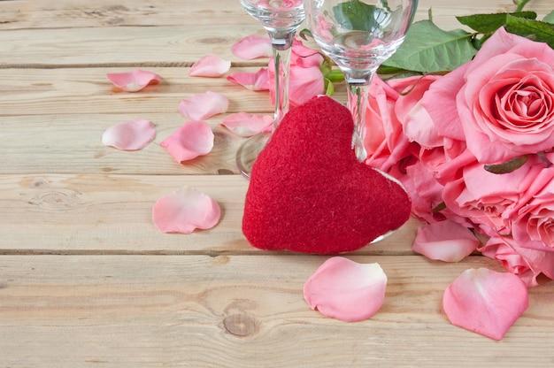 Rozenboeket, glazen voor champagne en hartsymbool op houten achtergrond