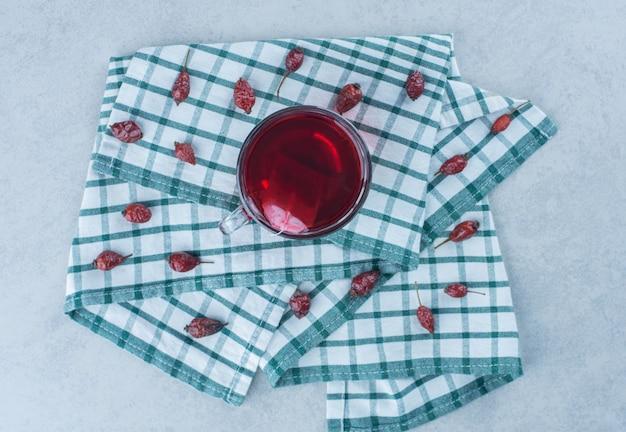 Rozenbottel fruit en thee op handdoek op marmer.