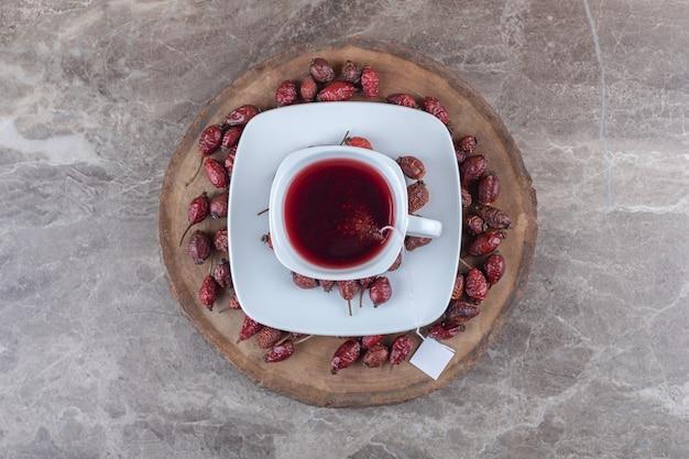 Rozenbottel fruit en thee op het bord, op de marmeren achtergrond.