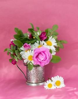 Rozenbottel roos en kamille boeket. zomerboeket van tuinbloemen. stilleven op de roze achtergrond