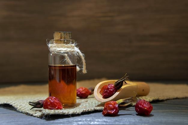 Rozenbottelolie op houten ondergrond met rood fruit