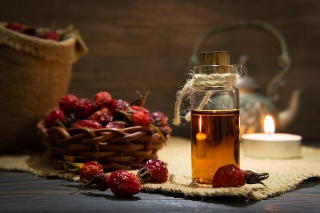 Rozenbottelolie op houten planken op een donkere achtergrond. de fles is vastgebonden met een koord met etherische olie van dogrose. de kaars is aan.