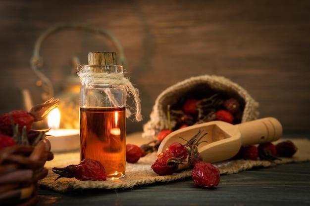 Rozenbottelolie op houten planken op een donkere achtergrond. de fles is vastgebonden met een koord met etherische olie van dogrose. zak met bessen.