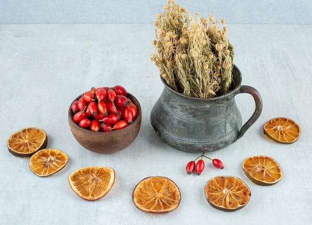 Rozenbottels, gedroogde sinaasappel en wijnruit op een stenen ondergrond.