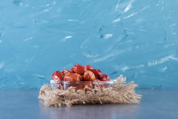 Rozenbottels in een glazen kom op de textuur op het marmeren oppervlak