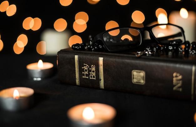 Rozenkrans, glazen op heilige bijbelboek en brandende kaarsen 's nachts tegen bokehlicht