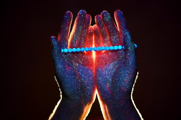 Rozenkrans in de hand, gebed. licht door de handpalmen in ultraviolet, god en religie, kralen. goddelijk licht door uw vingers, profeet mohammed