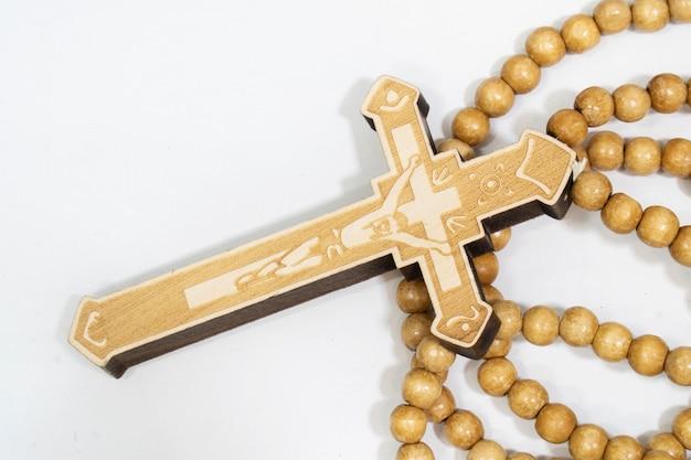 Rozenkrans kralen met kruis gemaakt van grijs hout op een witte achtergrond, geselecteerde focus op christus, smalle scherptediepte.