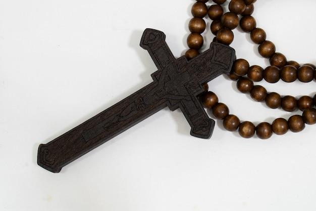 Rozenkrans kralen met kruis gemaakt van zwart hout op een witte achtergrond, geselecteerde focus op christus, smalle scherptediepte.
