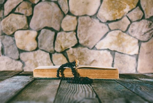 Rozenkrans met een kruisbeeld op een open oud boek