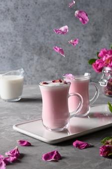 Rozenmaanmelk in glazen bekers en vallende rozenblaadjes op grijs. bovenaanzicht.