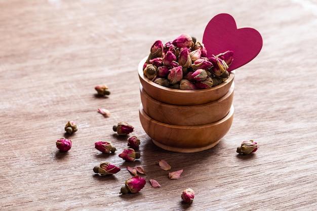 Rozerode droge roze knoppen in houten kom met bloemblaadjes en hartvormdecoratie op oude houten achtergrond.