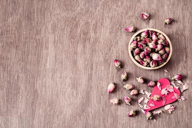 Rozerode droog nam knoppen in houten kom met bloemblaadjes op oude houten copyspace hoogste mening toe als achtergrond.
