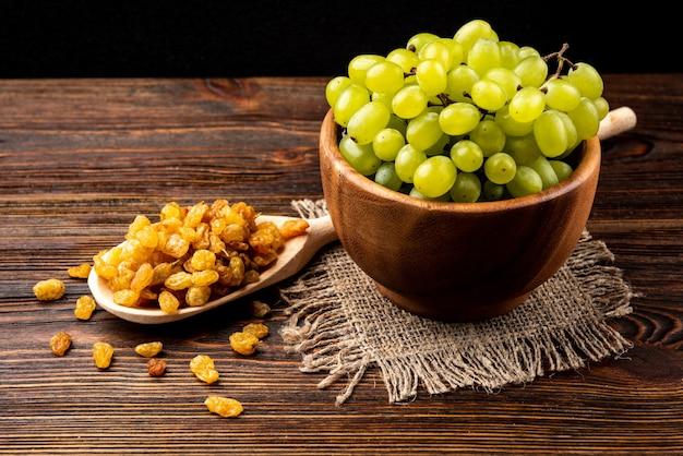 Rozijnen en groene druif op donkere houten