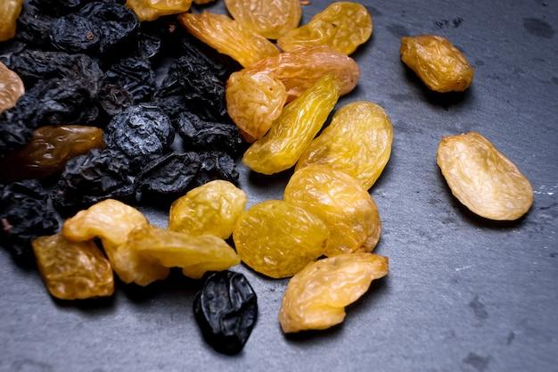 Rozijnen, geel, blauw, zwart, gouden rozijnen close-up op een zwarte achtergrond. vega food, macro foto