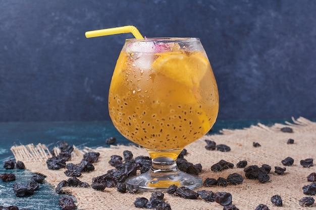 Rozijnen met citroenen met een kopje drank op blauw.