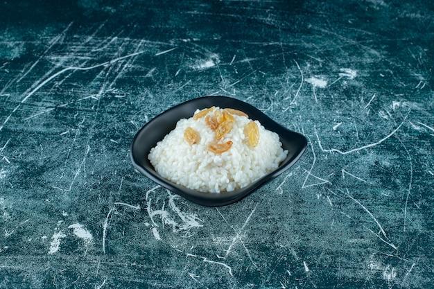 Rozijnen op een kom rijstpudding, op de blauwe achtergrond. hoge kwaliteit foto