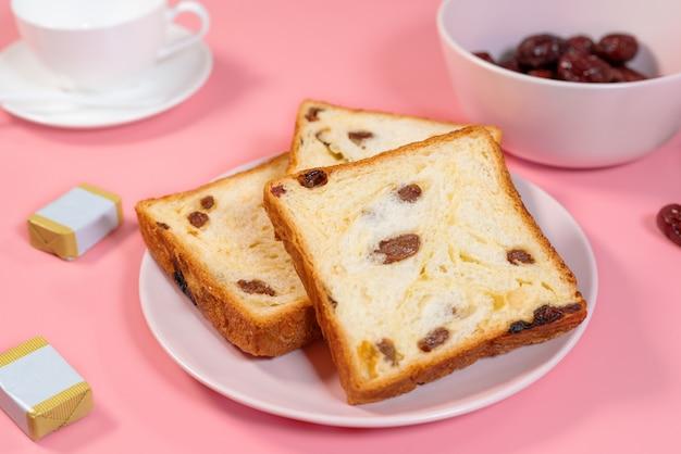 Rozijnen toast, boter en thee beker geplaatst op roze tafel