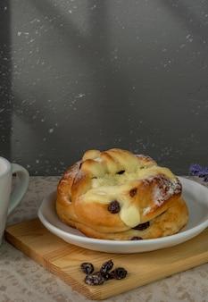 Rozijnenbroodje geserveerd met koffie