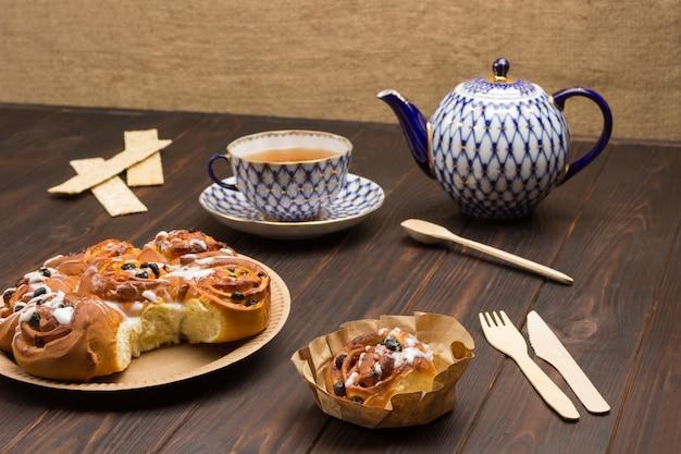 Rozijnenbroodjes in kartonnen plaat. theepot en kopje thee. donkere houten tafel. bovenaanzicht