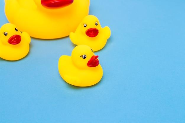 Rubber speelgoed van gele kleur mama-eend en kleine eendjes op een blauwe achtergrond. het concept van moederzorg en liefde voor kinderen, opvoeding en opvoeding van kinderen