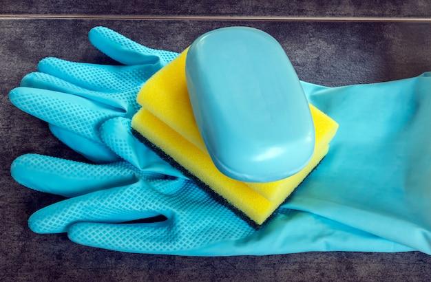 Rubberen handschoenen en cellulosesponzen klaar voor huishoudelijke reinigingstaken.