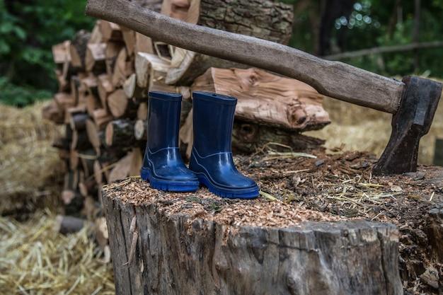 Rubberen laarzen voor kinderen op een boomstam in de buurt