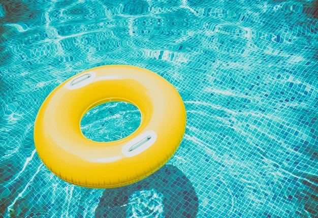 Rubberen ring drijvend in transparant blauw zwembad, retro getint