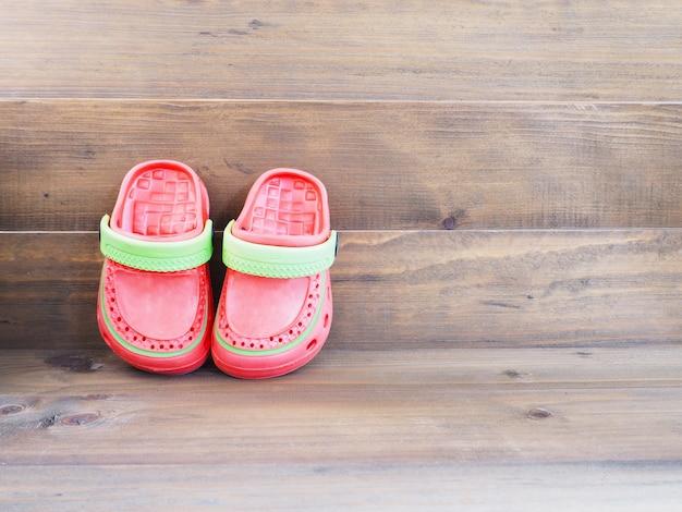 Rubberen sandalen voor kinderen op hout