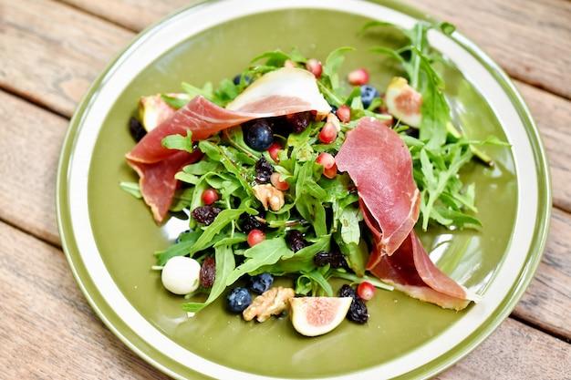 Rucola met prosciutto, parmaham en bessenfruit, gezonde voeding vol met goede groente en voeding, verfrissend voorgerecht.