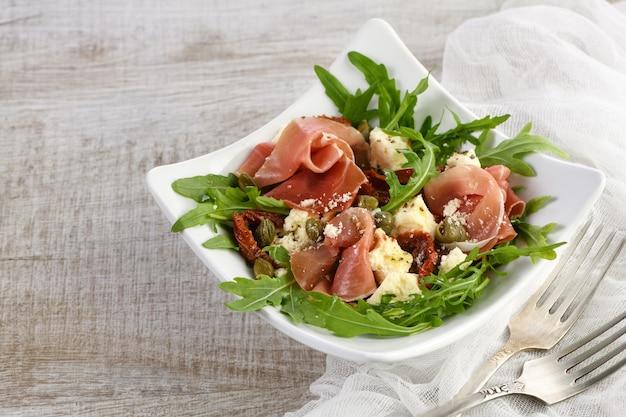 Rucola salade, parmaham met zongedroogde tomaten, plakjes mozzarella, kappertjes, op smaak gebracht met olijfboter en parmezaan. een gerecht voor degenen die hun gezondheid bewaken
