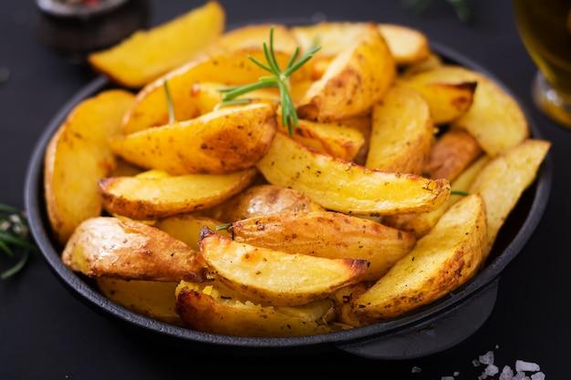 Ruddy gebakken aardappelwiggen met rozemarijn en knoflook op een donkere achtergrond.