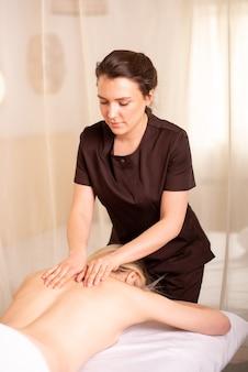 Rug- en schoudermassage door een glimlachende fysiotherapeut