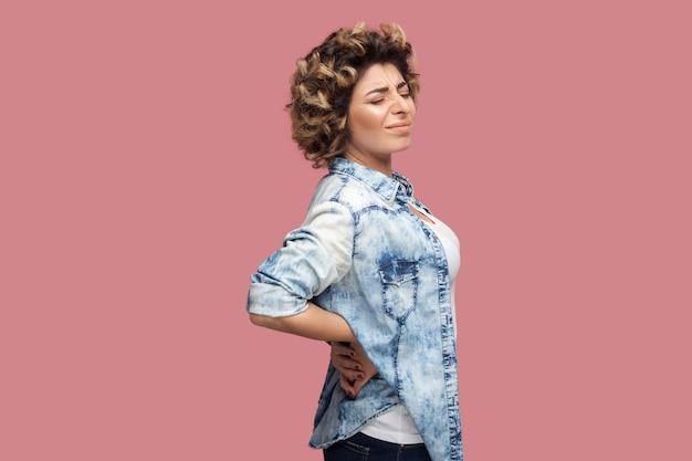 Rug-, nier- of wervelkolompijn. profiel zijaanzicht portret van trieste jonge vrouw met krullend kapsel in casual blauw shirt staande en pijn op rug verdragen. indoor studio opname, geïsoleerd op roze achtergrond.