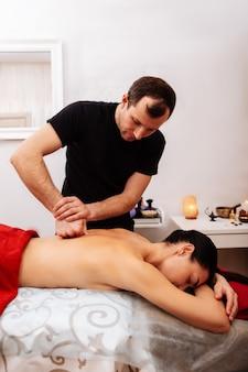 Rug spieren. kortharige meester in zwart t-shirt die zijn vuist gebruikt tijdens massage tijdens het opwarmen van de achterkant van een knappe vrouw