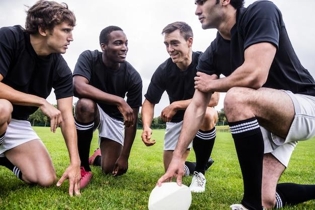 Rugbyspelers die hun tactieken bespreken