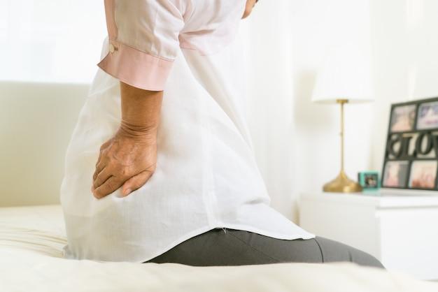 Rugpijn van oude vrouw thuis, gezondheidszorg probleem van senior concept