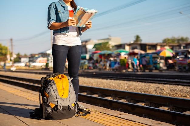 Rugzak en aziatische vrouw met kaart op het treinstation met een reiziger. reis concept.