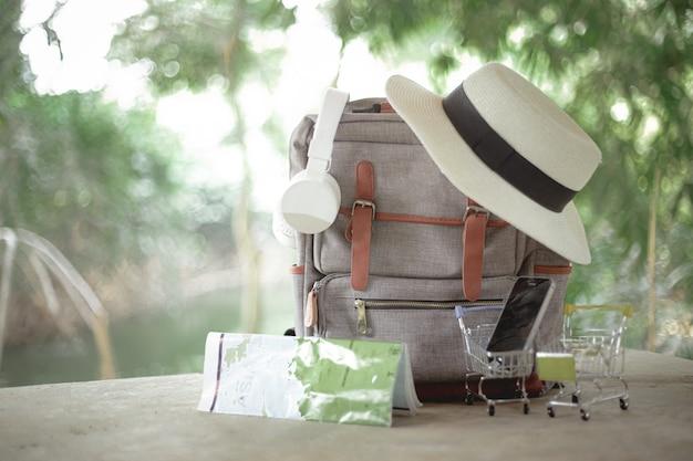Rugzak, hoed, kaart en koptelefoon op vakantie