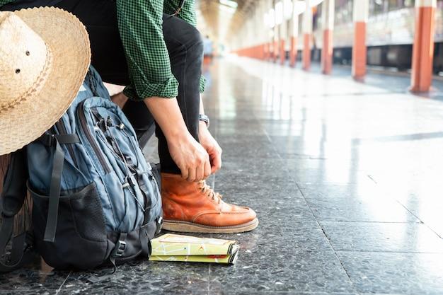 Rugzak, kaart en hoed op het treinstation met een reiziger. rugzakrugzak bond de schoen vast terwijl hij op de trein wachtte.